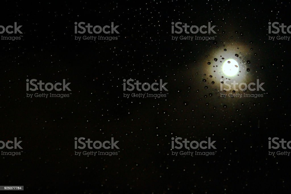 Raindrops with a full moon night sky background.