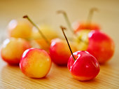 A macro closeup of a group of fresh rainier cherries on a wooden table.