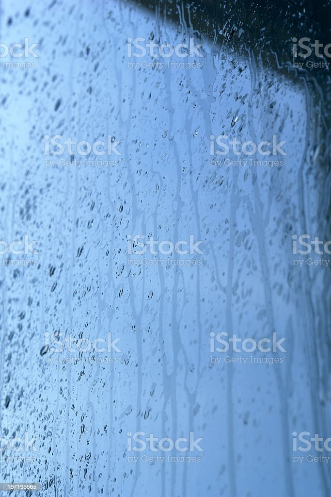 Raining cats and dogs, water drops flowing down the glass royalty-free stock photo