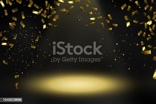 1051699126 istock photo raining gold confetti in spotlight 1045529896