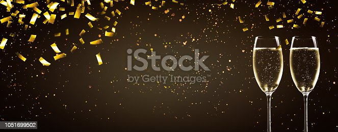 1051699126 istock photo raining gold confetti on champagne glasses 1051699502