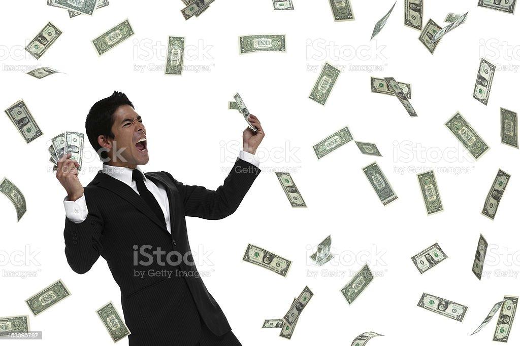 Raining money on celebrating business man looking to the side stock photo