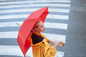 Woman holding umbrella and walking in the city.
