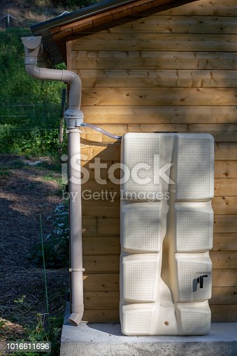 FRANCE, UZERCHE - JULY 12, 2018: Rainwater collection system with a plastic reservoir.