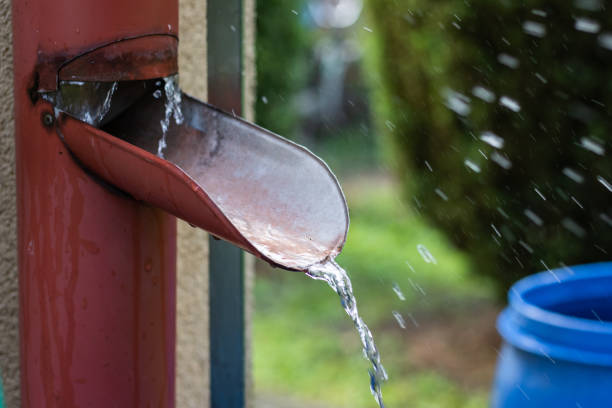 Rainwater flowing from roof gutter into barrel at garden stock photo