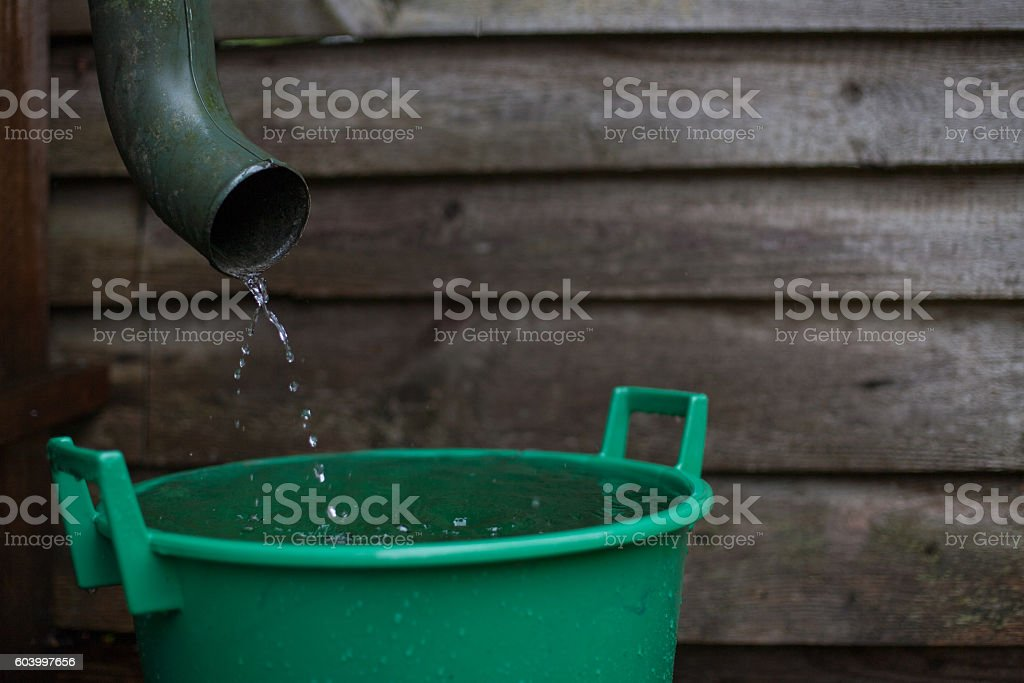 Rainwater shooting from a gutter into a water collecting reservoir stock photo