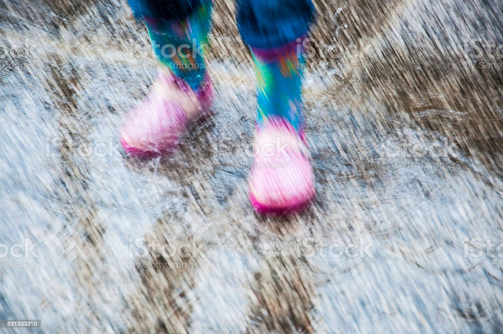 Photo of little girl\'s rubber boots standing in a puddle.