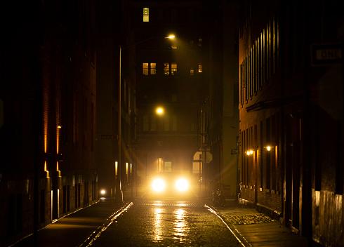Car headlights on a rainy city street at night.