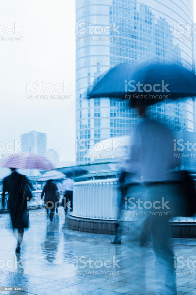 city commuters walking toward office buildings on a rainy morning