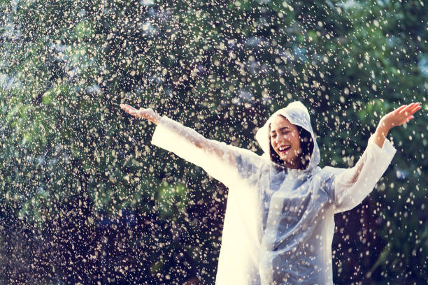 Rainy day asian woman wearing a raincoat outdoors. She is happy. Rainy day asian woman wearing a raincoat outdoors. She is happy. waterproof clothing stock pictures, royalty-free photos & images