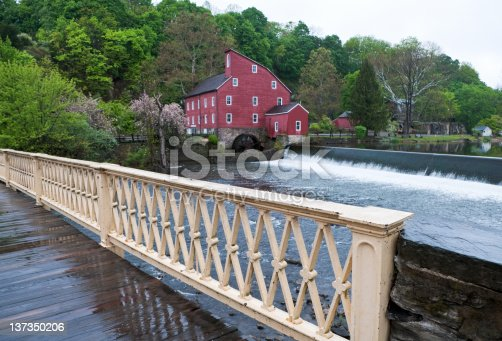 The old red mill in Clinton New Jersey shot from the one lane bridge that enters town.  Focus is on the railing and reflection on the wooden deck
