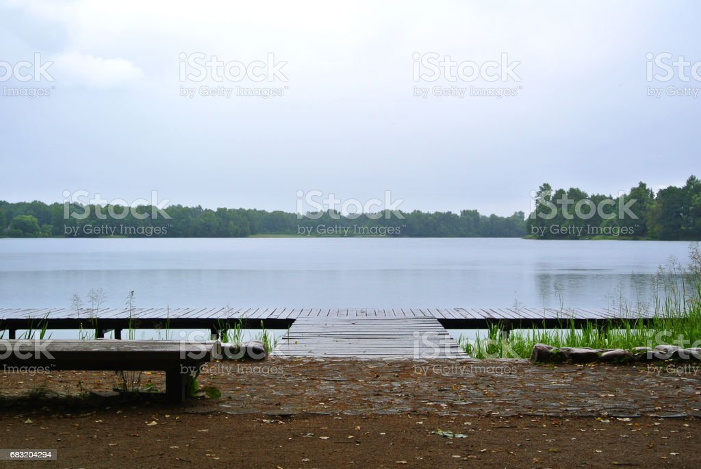 Rainy day at Trakai natural park, a view to a lake, forest, wooden bench and wooden quay, Lithuania. royalty-free stock photo