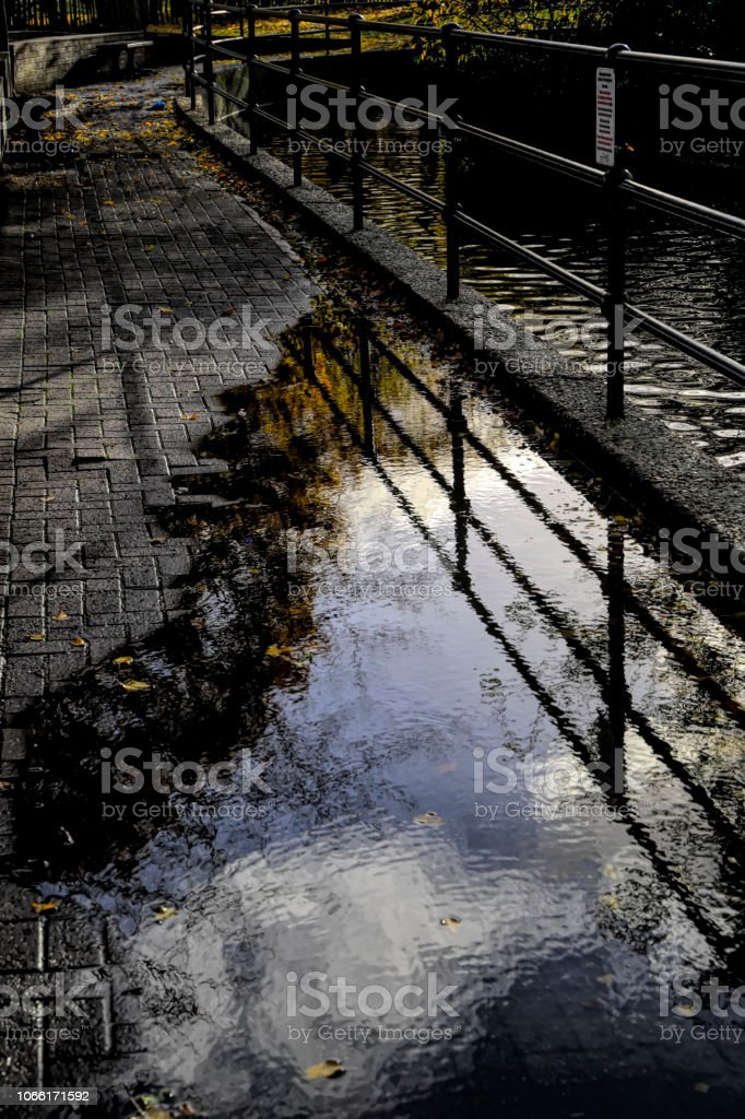 Rainy day clouds and sky reflected in puddle of water stock photo
