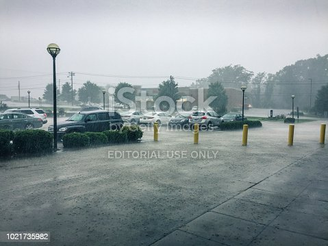 Walkertown, North Carolina, USA - August 2, 2018: creeks overflowed in Walkertown, NC, USA streets after days of pouring rain in Piedmont, North Carolina. The parking lot is covered with rainwater.