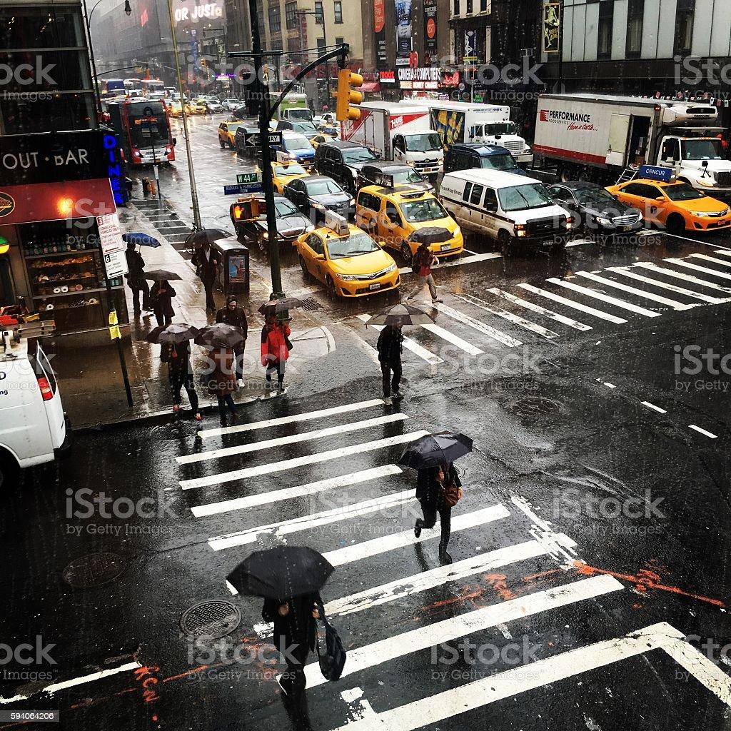 Rainy day on Manhattan, New York City Rainy day on Manhattan, New York City. People with umbrellas crossing the busy street. Asphalt Stock Photo