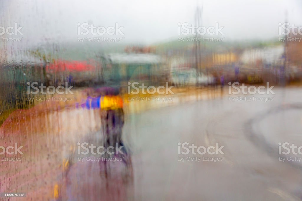 Rainy day photographed trough a window wheres focus is on on the...