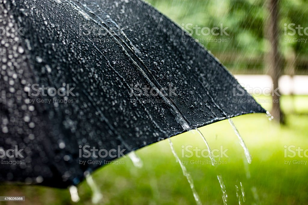 Rainy day. Raindrops falling on black umbrella outdoors. Spring, summer. stock photo