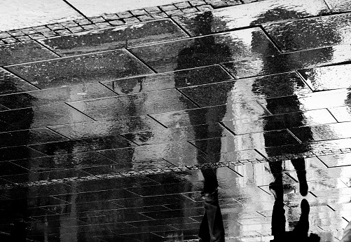 Reflection shadow of a couple walking in the rain in the city pedestrian zone in black and white