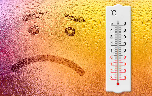 Rainy day. The sadness  emoji and thermometer on the wet window. Thermometer for measuring air temperature shows 15 degrees stock photo