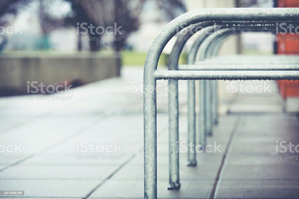 Rainy day - Wet & empty bike rack on sidewalk stock photo