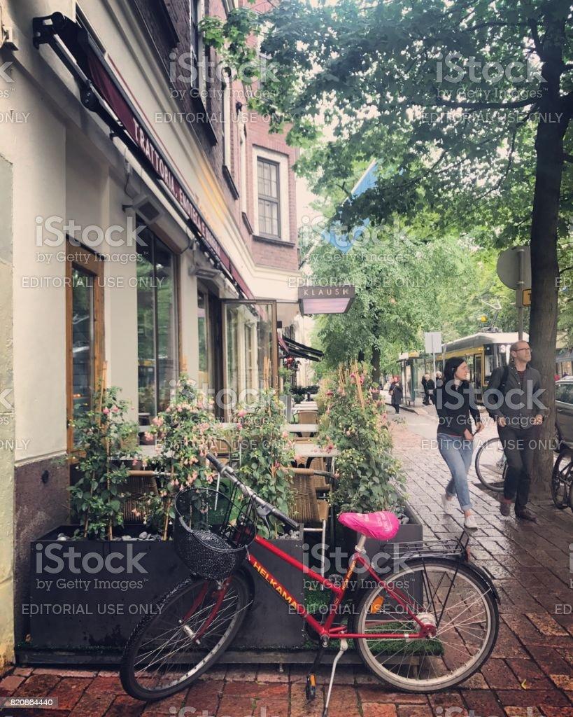 People walking under light rain in Helsinki, bicycle parked near...