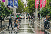 Melbourne, Victoria, Australia, March 31, 2019: Bourke Street in the centre of the city  is wet from recent rain while pedestrians and trams share the road space.