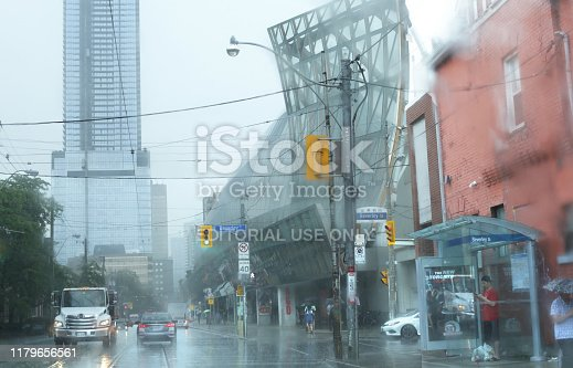 Toronto, Canada - August 17, 2019: Downtown traffic crosses the intersection on Dundas Street West at Beverley Street on a rainy morning. The Grange Park neighbourhood includes the Art Gallery of Ontario and Chinatown. Dundas Street is a major east-west arterial route with transit buses and streetcars.