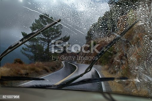 A vehicle driving through a rainy mountain road with the windshield wipers in motion.