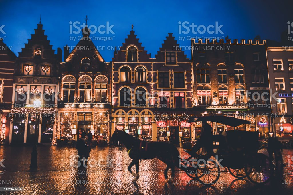 Une nuit pluvieuse avec Noël décorées bâtiments et chariot de cheval pour les touristes dans la ville médiévale de Bruges - Photo