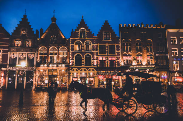 Rainy night with christmas decorated buildings and horse cart for tourists in medieval city of Bruges stock photo