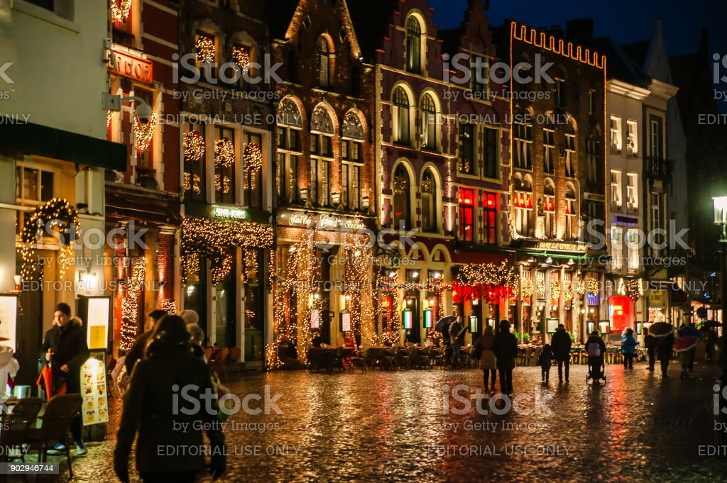 Une nuit pluvieuse avec Noël décoré de bâtiments dans la ville médiévale de Bruges - Photo
