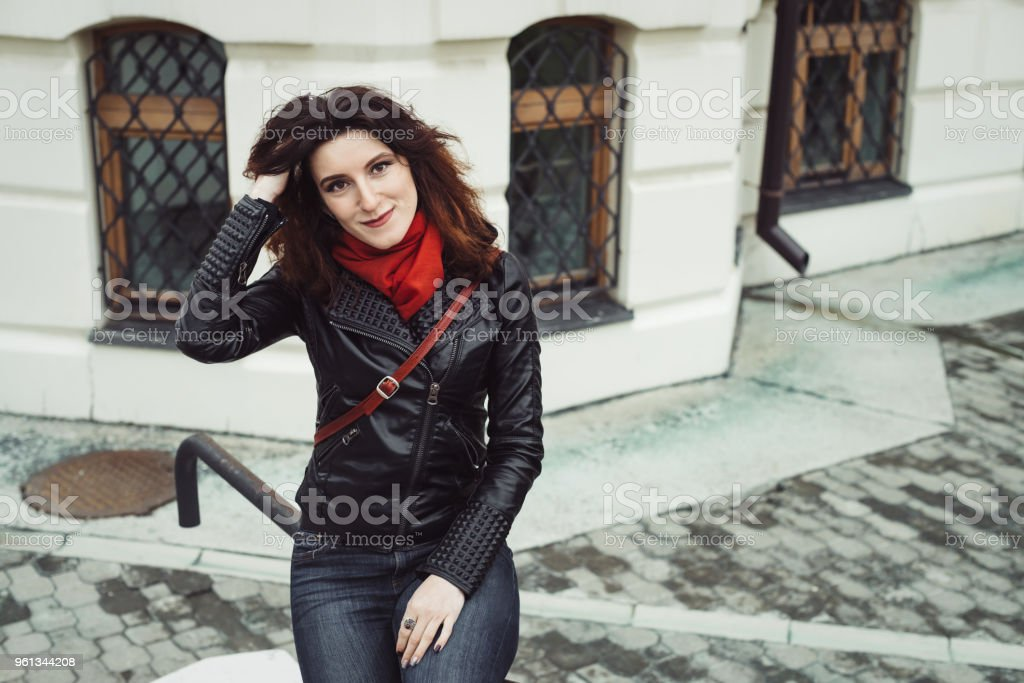 4056c51cb01 Rainy portrait of beautiful pensive girl with curly brown hair in black  leather jacket