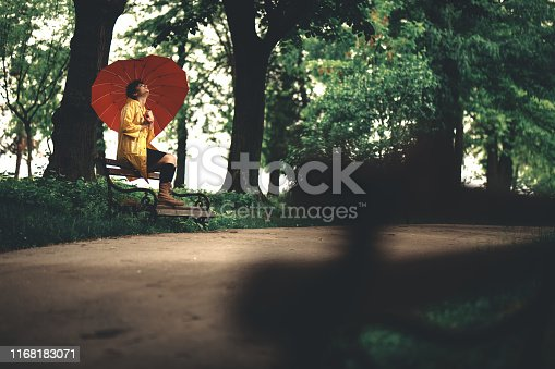 Young beautiful sad lonely caucasian woman sitting on a park bench at rainy day in public park.