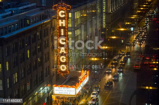 This is the view of a busy Chicago street during a rainy spring night.  Visible are a long line of cars on the street, streetlights, and a theater.