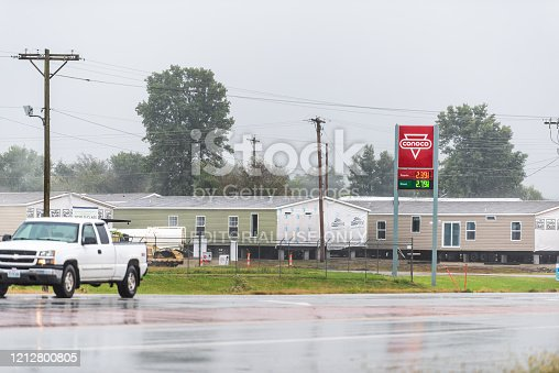 Chetopa, USA - October 15, 2019: Rainy street road in small town in Kansas countryside with red Conoco gas station sign