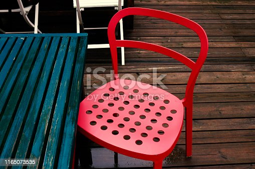 647209792 istock photo A rainy terrace with red steel chairs 1165073535