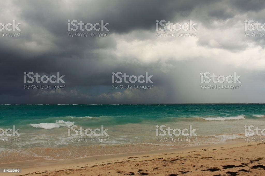 Rainy tropical storm coming from the atlantic ocean to the caribbean shore. Gloomy dark cloudy sky, turbulent sea waves. stock photo