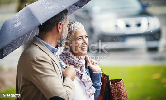 Closeup side view of late 40's couple walking home from shopping on a rainy day.They are crossing a street and walking to their car.