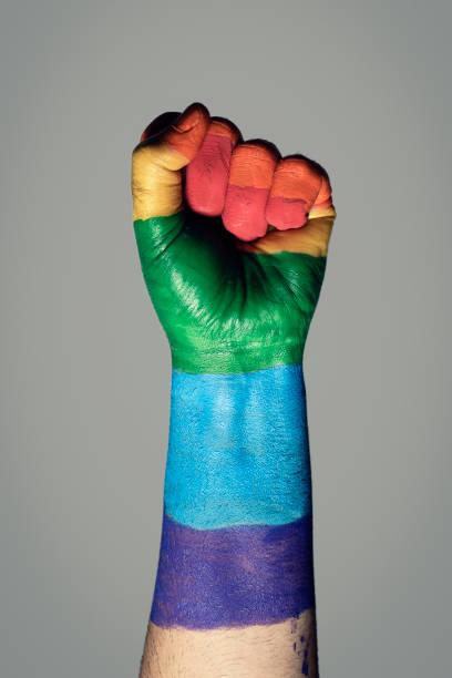 raised fist painted as a rainbow flag stock photo