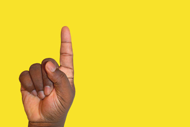 raised hand asking for permission or answering a question - finger pointing up against yellow background - vote sign stock photos and pictures