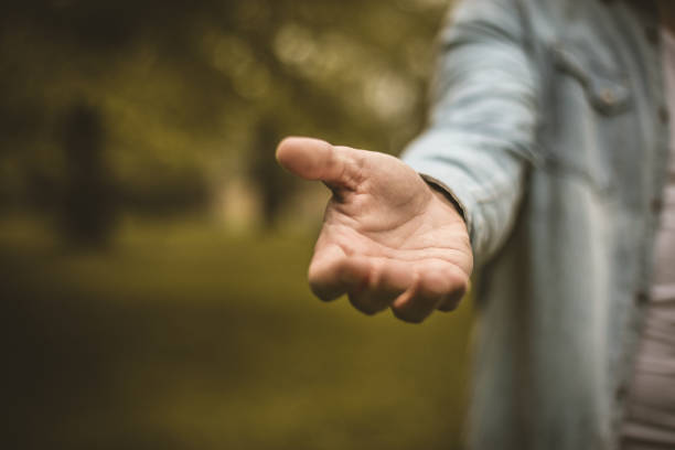 Raised hand. Young man in standing in park stretches his hand. Focus is on hand. Close up. a helping hand stock pictures, royalty-free photos & images
