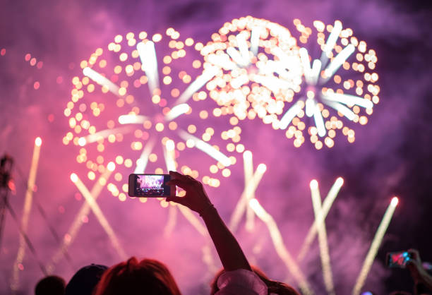 Raised hand with shooting horizontal night fireworks sky video smartphone . Colorful bright background entertainment with light and laser show. Raised hand with shooting horizontal night fireworks sky video smartphone . Colorful bright background entertainment with light and laser show. fireworks photos stock pictures, royalty-free photos & images