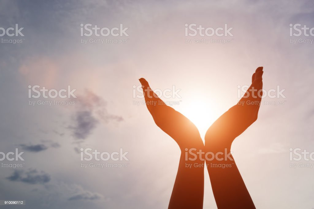 Raised hands catching sun on sunset sky. Concept of spirituality, wellbeing, positive energy stock photo