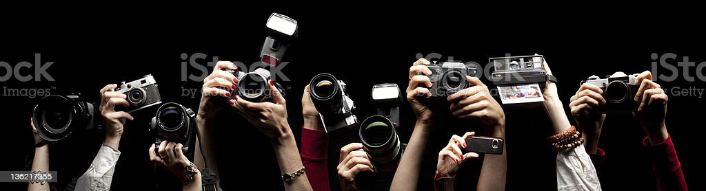 Raised hands holding photocameras Raised hands holding different photocameras (old-fashioned and contemporary) isolated on black Paparazzi Photographer Stock Photo