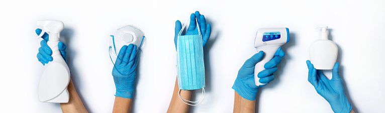 Raised hands in medical gloves holding masks, sanitizers, soap, non contact thermometer on white background. Banner. Copy space. Health protection equipment during quarantine Coronavirus pandemic.