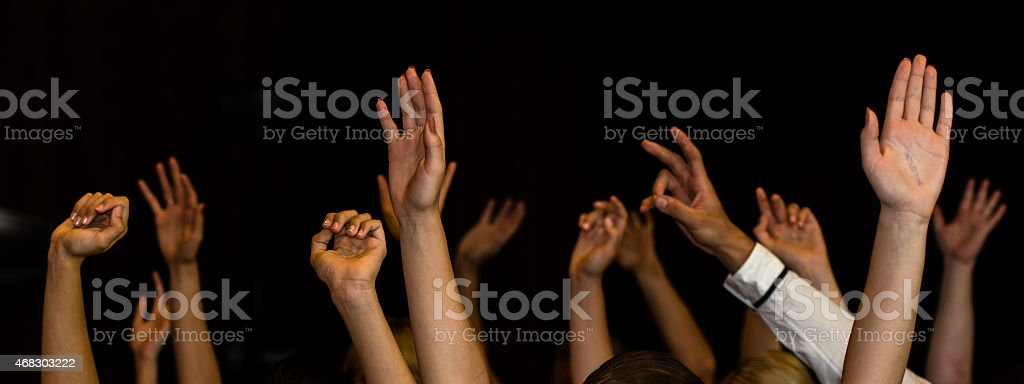 Raised hands of male and female participants of the meeting stock photo