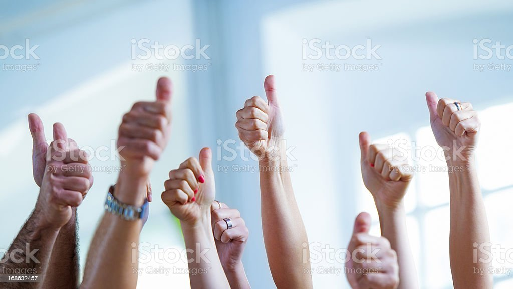 Raised hands with thumbs up royalty-free stock photo