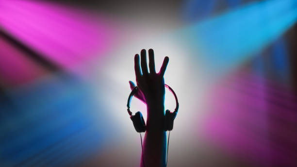 DJ raised his hand. Headphones in his hand DJ raised his hand. Headphones in his hand. electronic music stock pictures, royalty-free photos & images