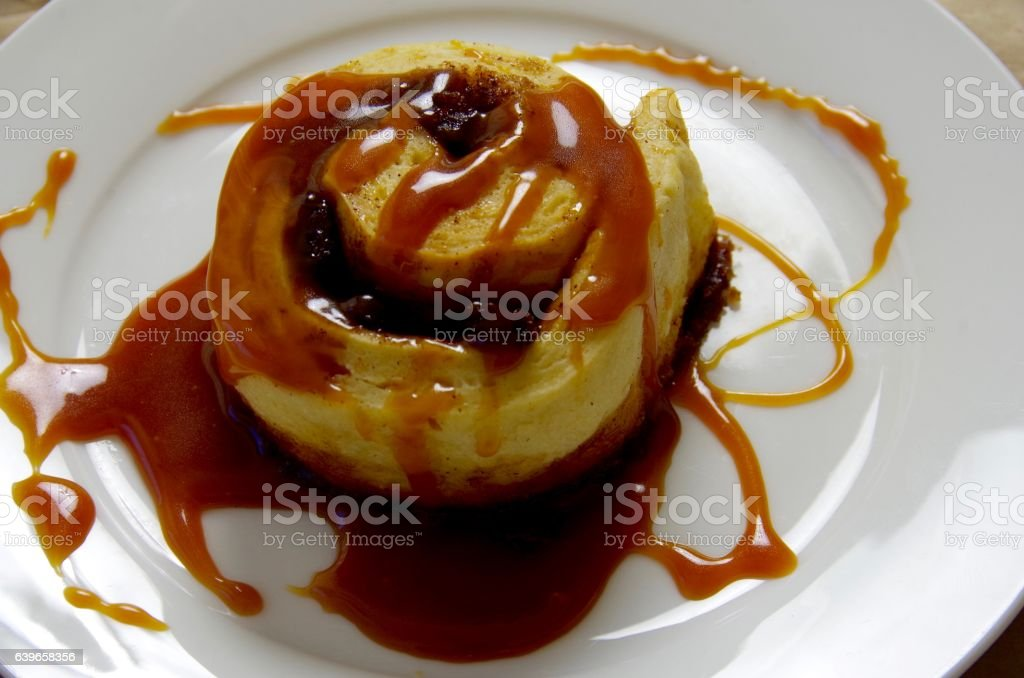 Raisin-cinnamon bun covered with sticky caramel sauce stock photo