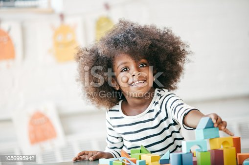 3 years old girl playing with colorful blocks